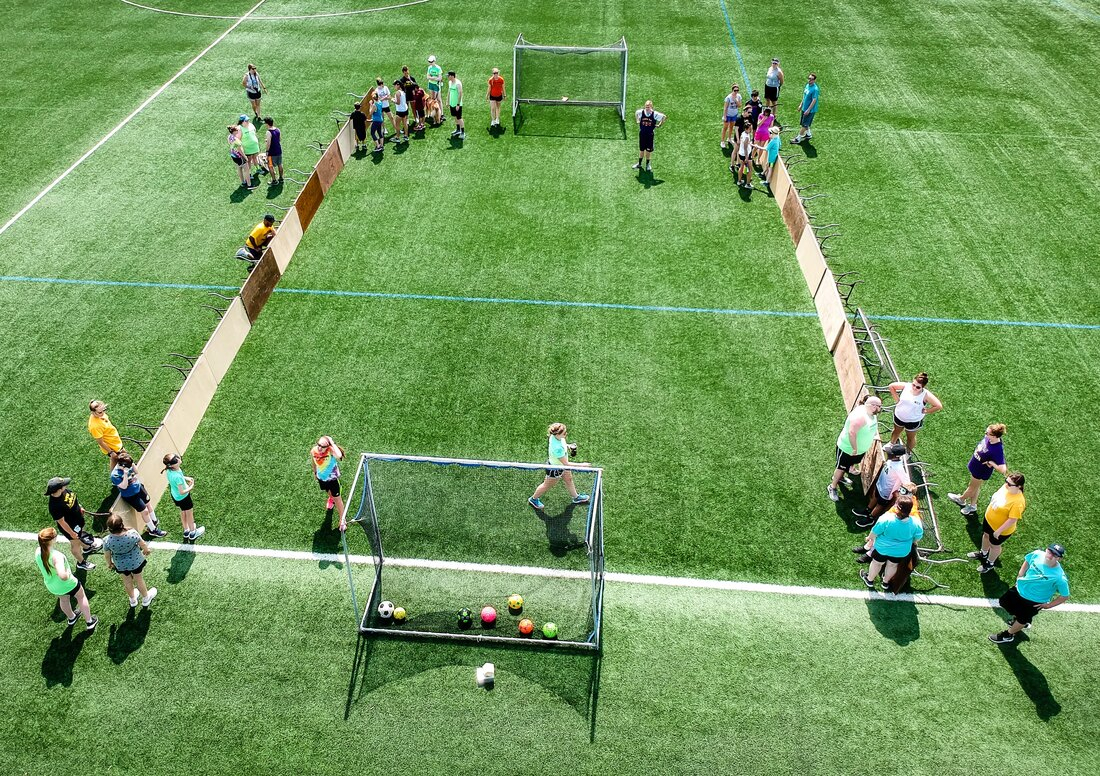 Aerial photo of athletes playing futsal on a soccer field.
