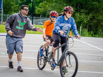 Photo of a coach helping send off a tandem bike team.