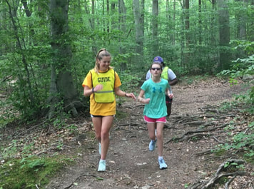 Photo of a coach guide running with an athlete in the Gordon Natural Area